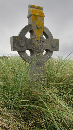 Celtic cross amidst the overgrown grasses in the cemetery on the Aran Island of Inisheer in Ireland