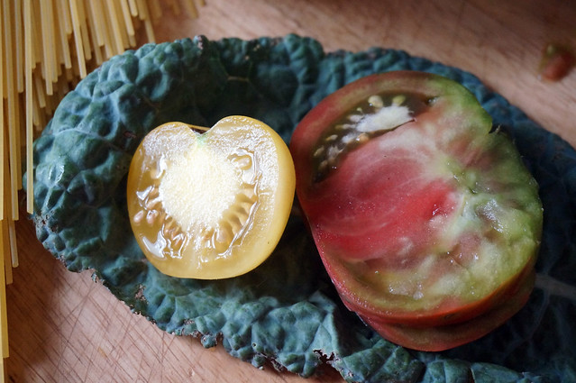 A single leaf of kale lies on a wooden countertop, serving as a makeshift platter for sliced yellow and red tomatoes.