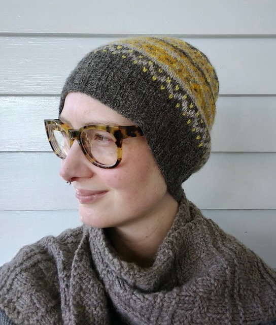 An image of a woman's upper torso and head in front of a blue weatherboard background. She wears a handknit Fair Isle hat in yellows and greys, with a textured handknit grey scarf.