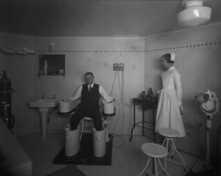 Château Laurier Hotel - man soaking his hands and feet in Schnee baths, therapeutic department, Ottawa, Ontario / Hôtel Château Laurier - un homme trempe ses mains et ses pieds dans des bains Schnee, service thérapeutique, Ottawa (Ontario)