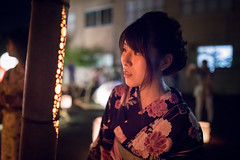 Young woman in yukata looking at candle lights in bamboo pole