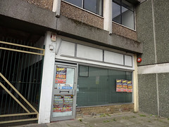 "A small, blocky ground-floor shop unit with a tall gate next to it made from metal bars with a large backwards ""Z"".  The unit is clearly empty, with funfair posters all over the windows and a sign on the door reading ""Warning / Construction site / Keep out""."