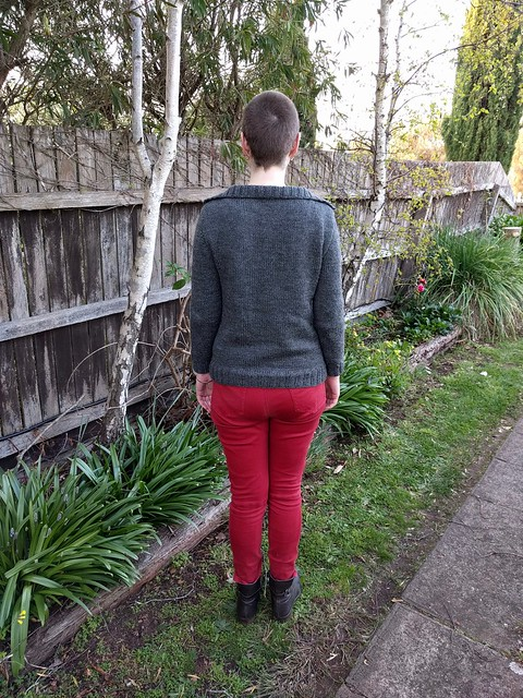 Woman stands against garden fence. She wears a grey handknit cardigan, red jeans and ankle boots.