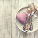Love, valentine's day or eating concept with vintage cutlery, plate and plush heart on a wooden background. Top view with copy space