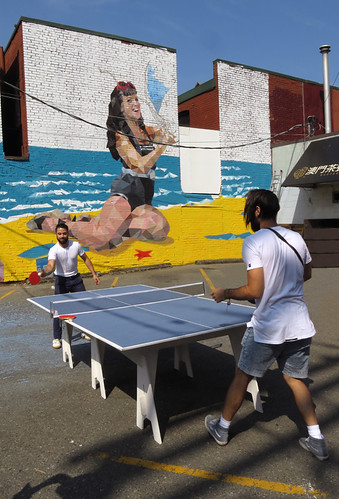 A game of Ping Pong in front of a mural wall painting at the Mural Fest just off Main St. in Vancouver