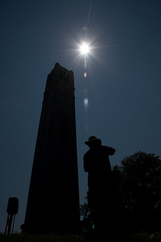 A photographer takes photos of the Belltower and the eclipse.