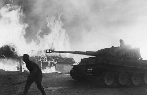 German Pz. Kpfw. VI Tiger passing burning homes near Kursk 1943.