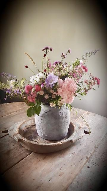 Kruik met bloemen in houten schaal