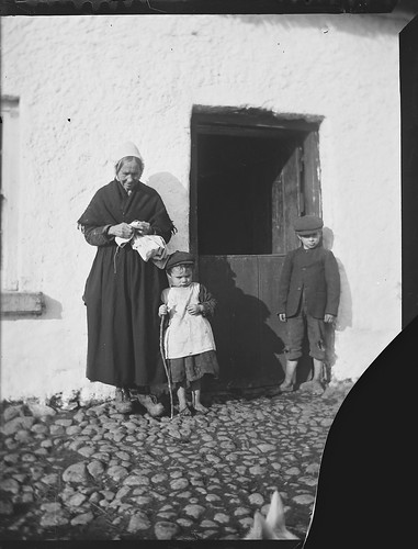 Old woman and two young boys in doorway of thatched cottage