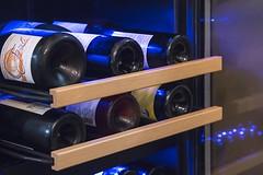 wine bottles on racks in a wine cooler / refrigerator