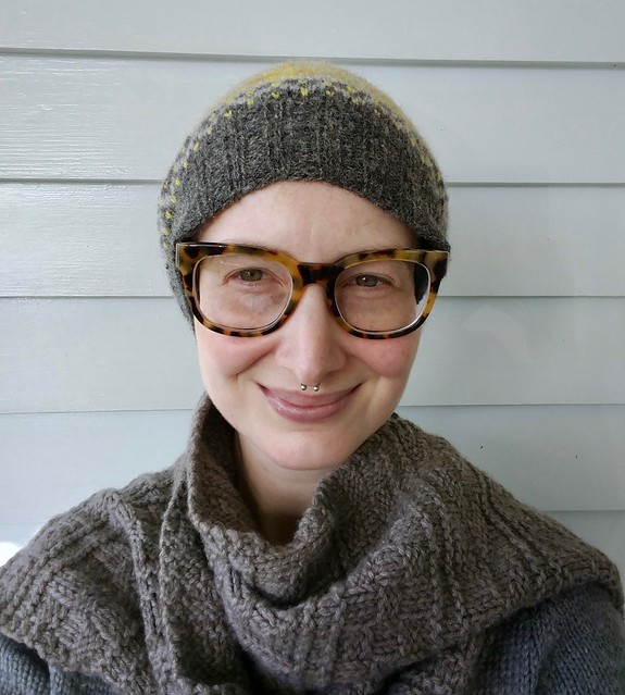 Woman wears colourwork handknit hat and scarf.