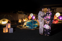 Mother and daughter in yukata standing in cadle lights in paper umbrellas and boxes