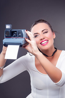 Youth Lifestyle Concepts. Portrait of Happy Smiling caucasian Brunette Female with Instant Camera and Print. Posing Against Gray