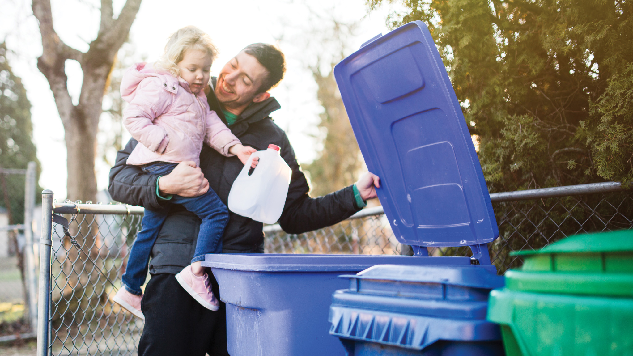 Father helps his daughter recycle a plastic bottle