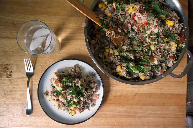 An overhead shot showing a plated serving of pilaf, a pan full of the remnants, and a glass of water. It's very simple, and would probably irk Sandra Lee with her elaborate tablescapes.