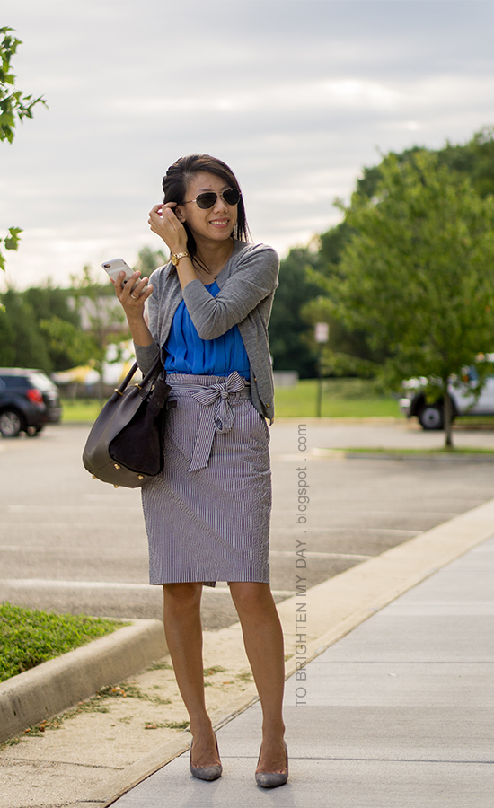 gray cardigan, bright blue pleated top, blue seersucker pencil skirt with bow, gray suede tote, gold watch, gray suede pumps