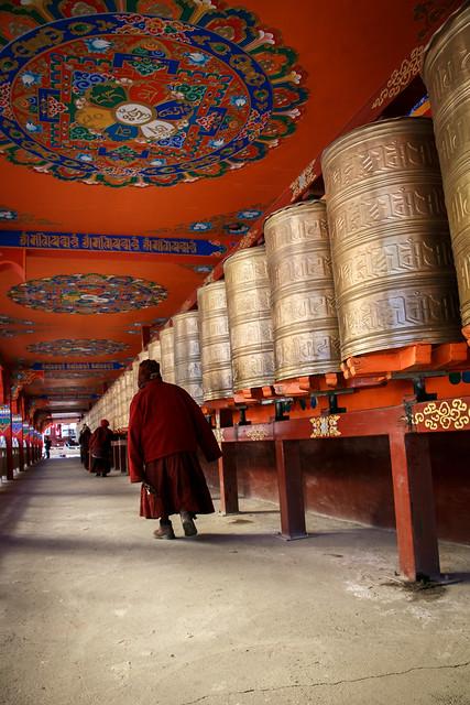 A monk and prayer wheels in Yarchen Gar アチェンガルゴンパ マニ車が並ぶ建物をコルラするお坊さん