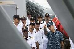 Boatswain's Mate 2nd Class Thomas Vongpanya discusses the use of the 11-meter RHIB boat during visit, board, search and seizure operations during a tour of USS Pearl Harbor (LSD 52) by Indian Navy sailors, Aug. 25. (U.S. Navy/Ensign Kris Rodriguez)