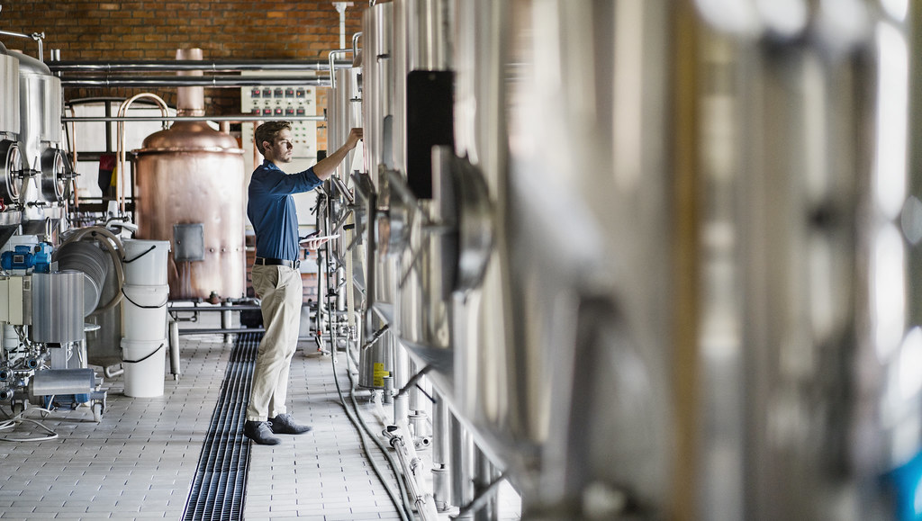 A worker checking a dial in a microbrewery