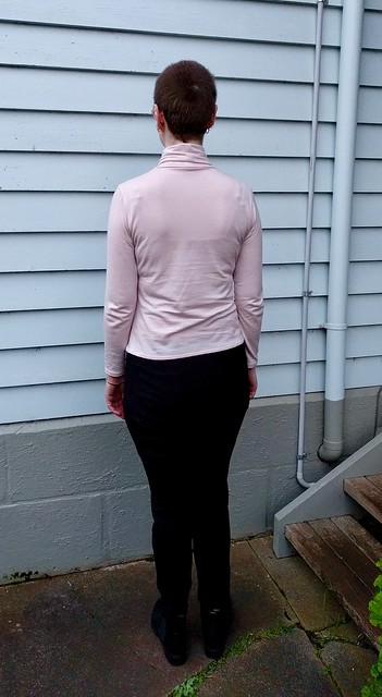 An image of a woman standing in front of a blue weatherboard background. She is wearing a pink merino turtleneck long sleeve tee, black ponte pants and black ankle boots. Her back is to the camera.