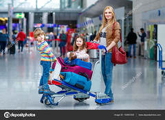 Mother and two little kids children at the airport, traveling together