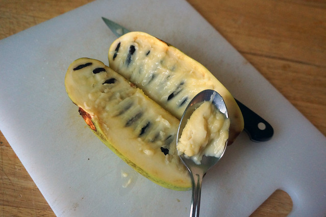 A pawpaw, split down the middle lies on a plate, showing two rows of shiny black-brown seeds embedded in soft, pale yellow flesh. A spoonful of the flesh sits on top of one half, showing the fruit's custardy texture.