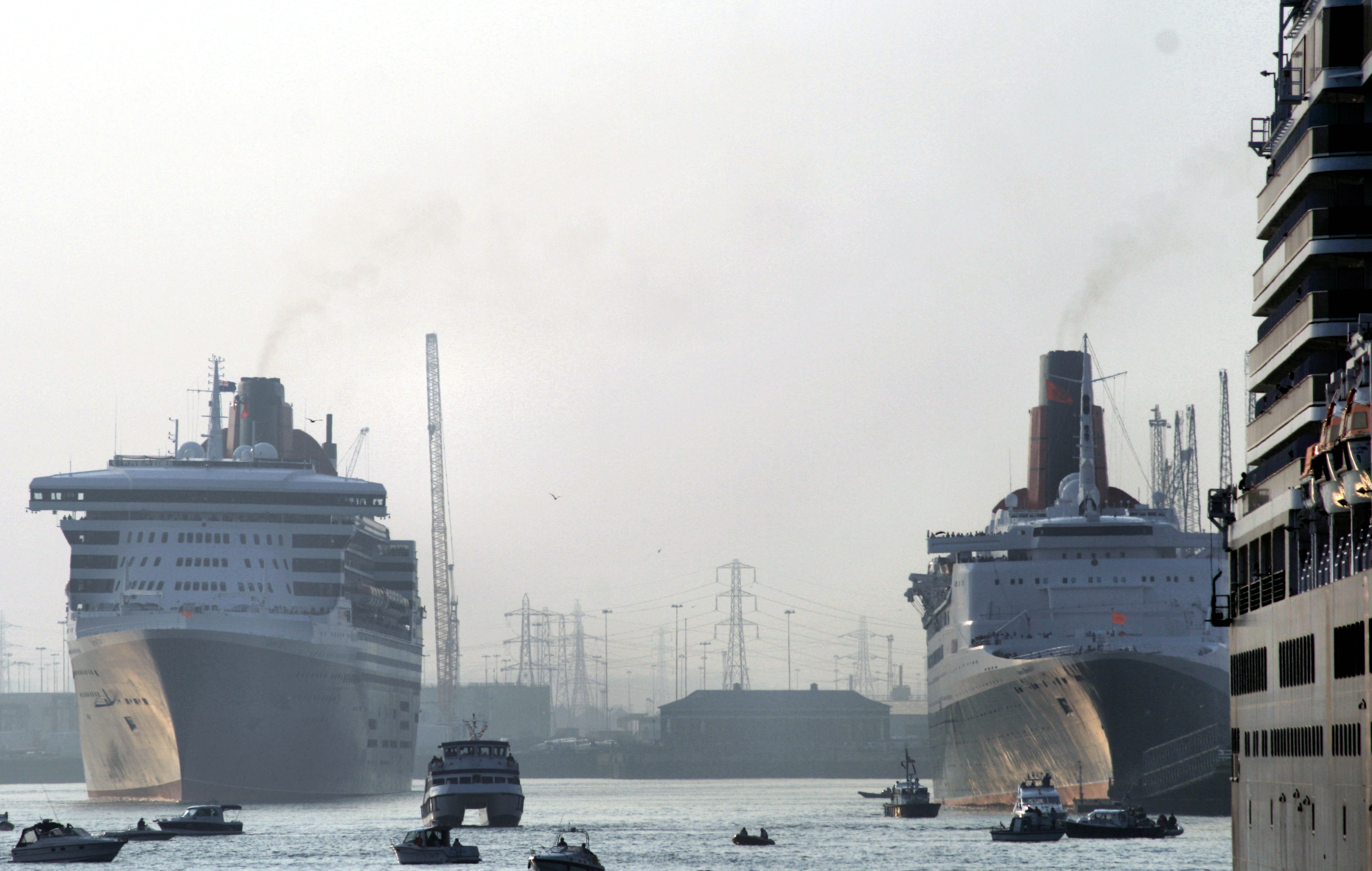 RMS Queen Mary 2 next to QE2 with stern of MS Queen Victoria on far right.