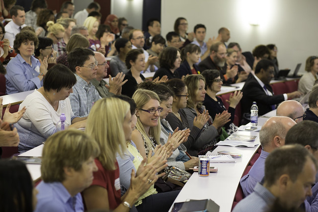 An enthusiastic audience applauds an inspiring talk