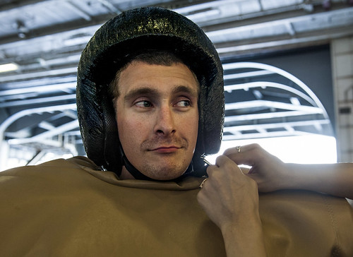 Sun, 08/20/2017 - 22:01 - 170820-N-RZ514-048 ATLANTIC OCEAN (Aug. 20, 2017) Fire Controlman 2nd Class Thomas Jeffries gets help donning a sumo suit during a Tiger Cruise aboard the aircraft carrier USS George H.W. Bush (CVN 77). The ship and its carrier strike group are transiting home from a scheduled seven-month deployment in support of maritime security operations and theater security cooperation efforts in the U.S. 5th and 6th Fleet areas of responsibility.  (U.S. Navy photo by Mass Communication Specialist Seaman Jennifer M. Kirkman/Released)