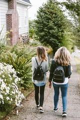 2chicas-paseando-calle-mochilas