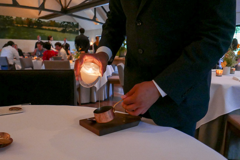 Melted beef tallow candle is poured over next course