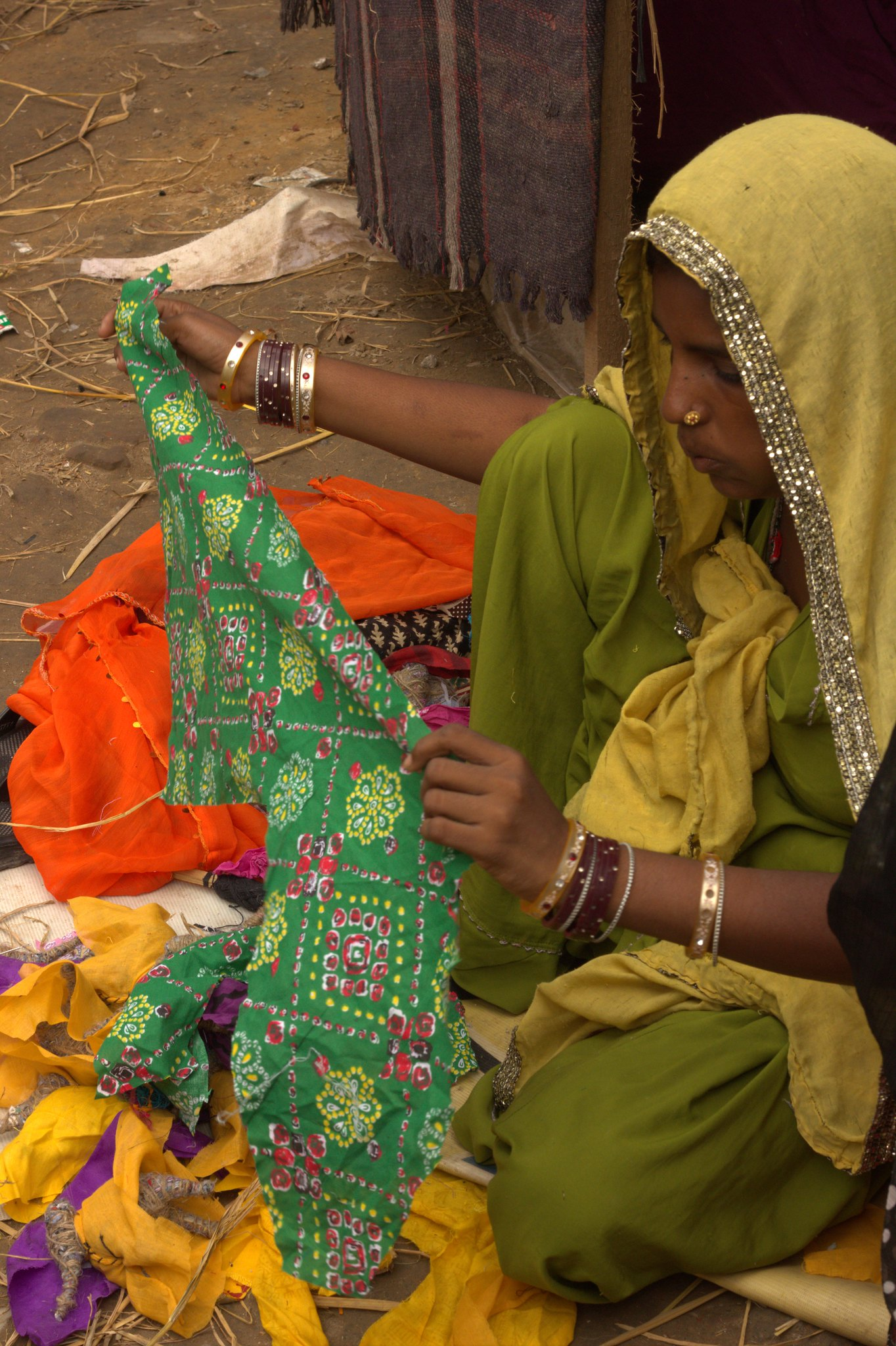 A seamstress sews dresses for puppets at Kathputli Colony
