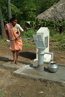 Woman pumping water from well.