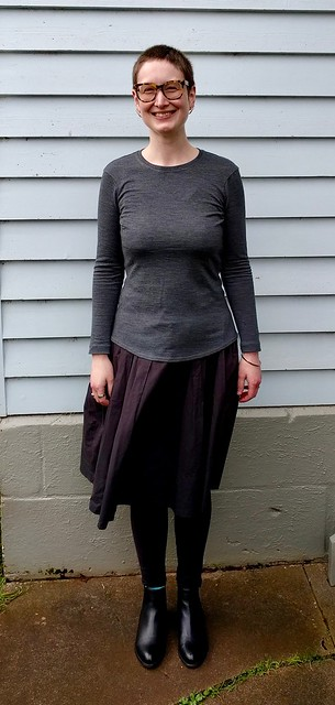 Woman stands against weatherboard house. She wears a grey merino long sleeve tee, black skirt and ankle boots.