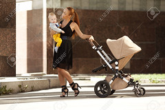 Fashionable modern mother on a city street with a pram. Young mother walks with a child in the city. Beautiful young woman with a child in a baby carriage