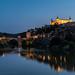 Blue hour shot of the Alcázar, River Tagus and the Puente de Alcántara in Toledo.