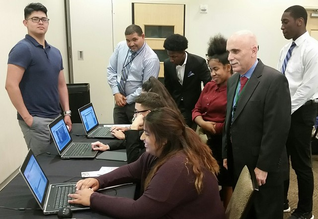 Dr. Ken Morlino, MBA program chair at WilmU (right front), and Carlos Cotto (center, back),  a board member of ASPIRA DE and a BNYMellon vice president, look on as students competed in a complete business simulation at the 2017 Millennial Summit.