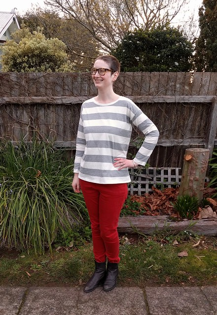 Woman stands against garden fence. She wears a long sleeve striped tee, red jeans and ankle boots.