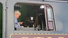 Steam train conductor checking his iPhone