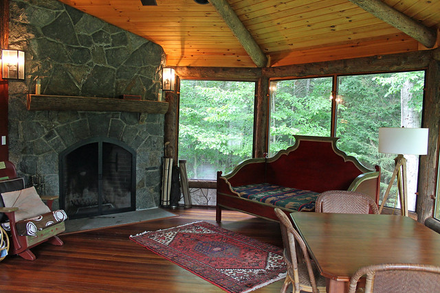 Stone fireplace, dining table and sleeping lounge bed.