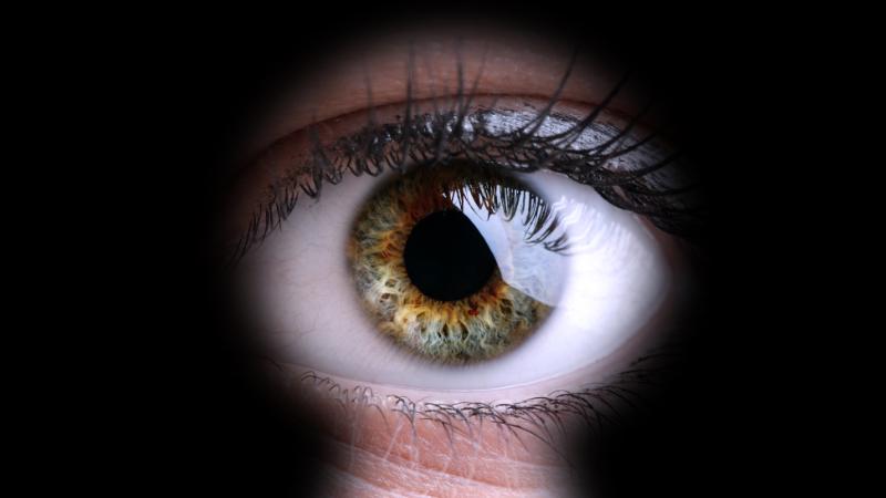 An eye looking through a keyhole
