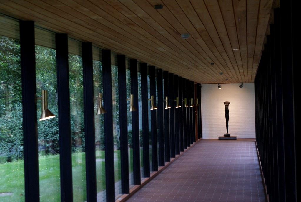 Long couloir de verre noyant le Musée d'art contemporain Louisiana (Copenhague) dans la nature.