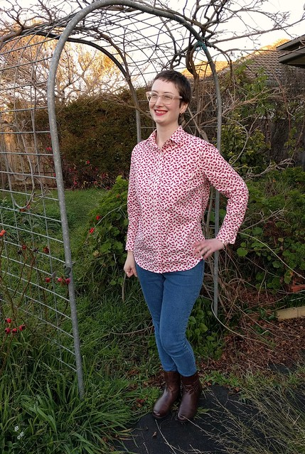 A woman stands in a garden archway. She wears a watermelon print button up shirt, jeans and ankle boots.
