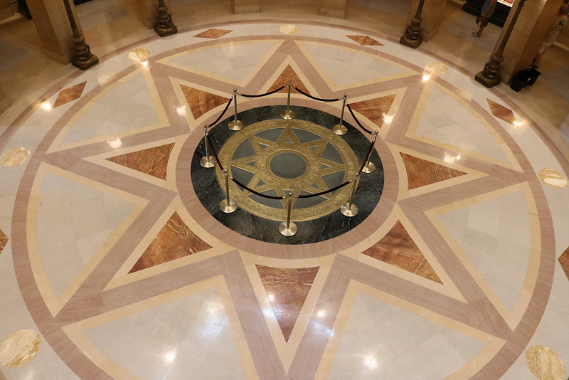 looking down at the floor with a gold, 8-pointed star surrounded by 3 circles and a larger 8-pointed star