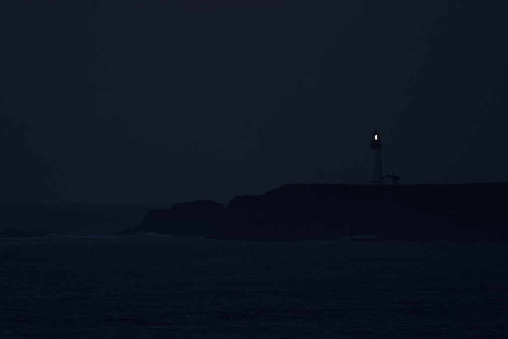 The lighthouse at Yaquina Head shines in the darkness in Newport, Oregon