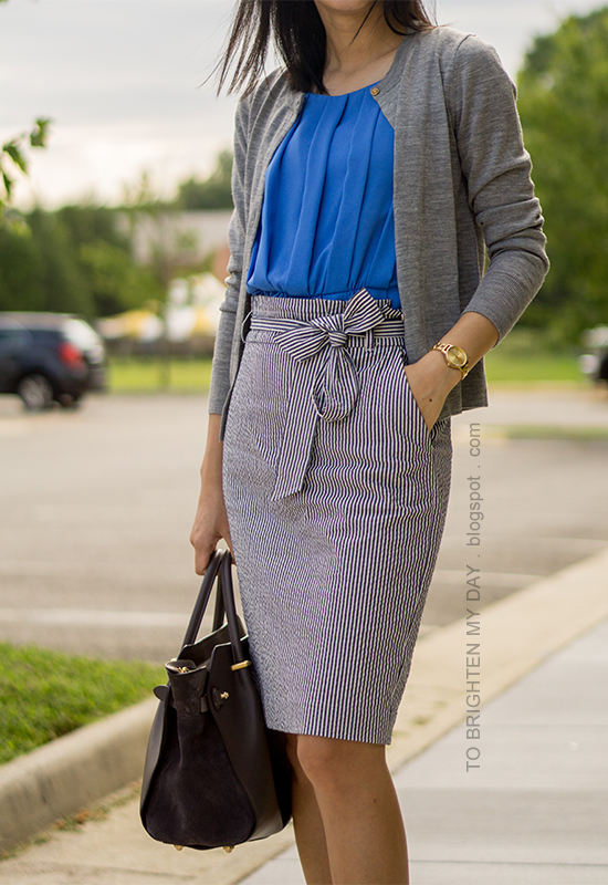 gray cardigan, bright blue pleated top, blue seersucker pencil skirt with bow, gray suede tote, gold watch