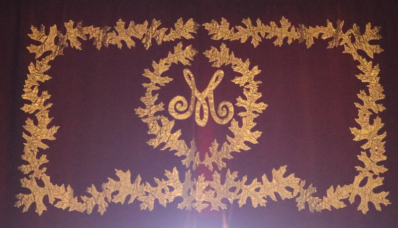script gold cloth surrounded by a circle of gold oak leaves, surrounded by a rectangle of leaves, on a maroon velvet(?) curtain above a window