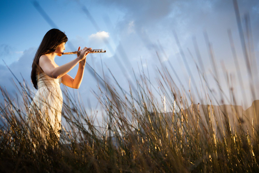 Photo of flutist playing outdoors
