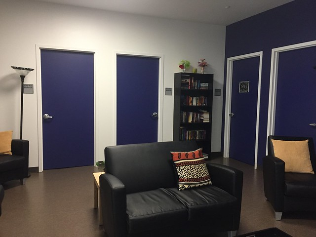 Photo of a room with black leather seats, a book case and four blue doors.