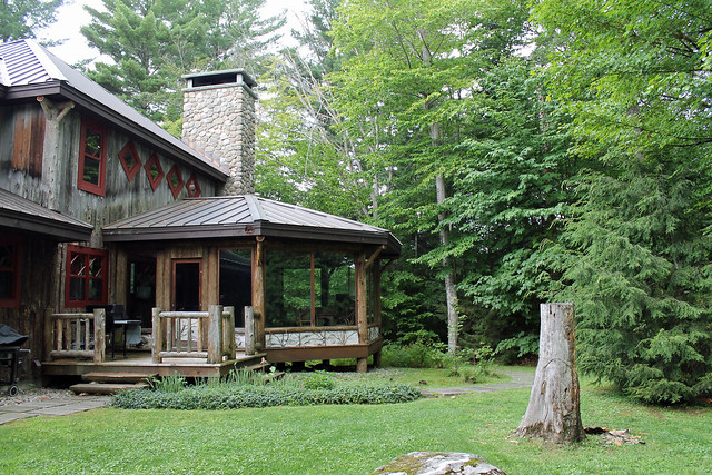 Gorgeous enclosed sun room/porch with in-floor heating, stone fireplace and wrap around glass.